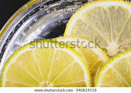 Slices of lime and lemon in soda water. Lime Cocktail. The liquid drink. Bubbles of carbon dioxide. The background texture. Selective focus. Tropical citrus fruit. Macro Lime. Ingredient - stock photo
