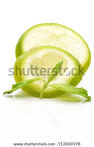 Slices of lime with a branch mint, close-up - stock photo