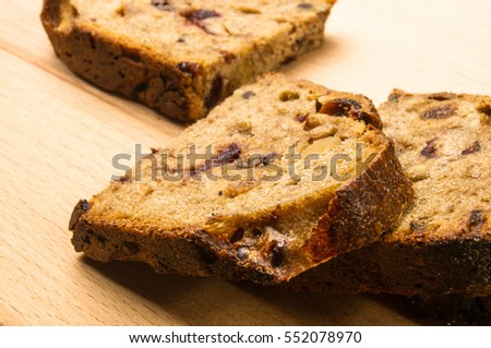 Slices of malt bread handmade with nuts, raisins and cranberries on wooden background
