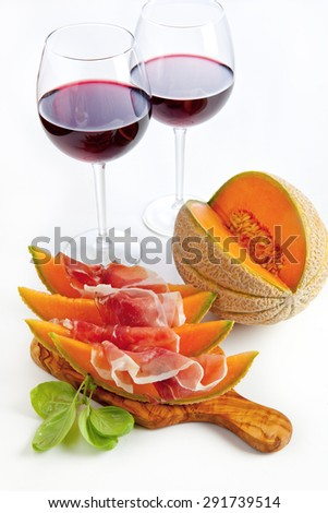 Slices of melon cantaloupe with prosciutto ham & wineglasses with wine. healthy snack - stock photo