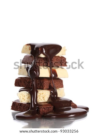 Slices of milk and white chocolate bar poured chocolate isolated on white - stock photo