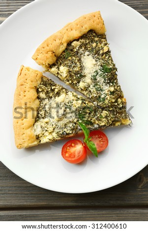 Slices of open pie with spinach and tomato cherry on plate close up - stock photo