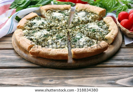 Slices of open pie with spinach and tomato cherry on table close up - stock photo