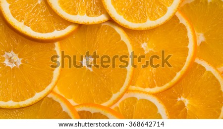 slices of oranges laid out in the form of background closeup - stock photo