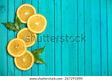 Slices of oranges on a turquoise  wooden background. Selective focus, copy space background, top view - stock photo