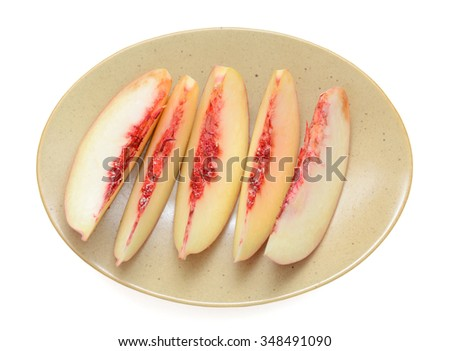 slices of peach on plate isolated on white  - stock photo