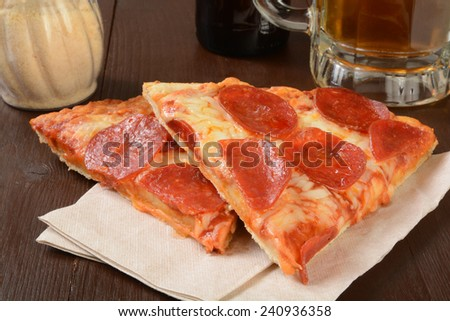 Slices of pepperoni pizza with a mug of beer - stock photo