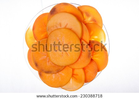 Slices of persimon fruit, placed on a plate. with white background - stock photo