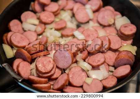 slices of polish sausage fired with onion - stock photo