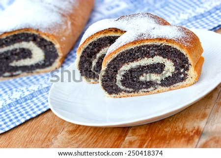 Slices of poppy seeds strudel on plate and strudel of poppy seeds on table - stock photo
