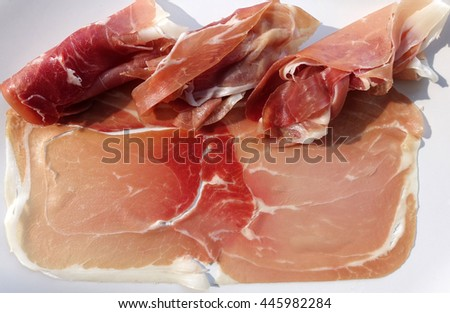 Slices of prosciutto on a white background. A peace of prosciutto. Italian prosciutto. Prosciutto close up.