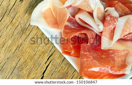 Slices of prosciutto on old wood