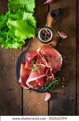 Slices of Prosciutto on old wooden background.Top view - stock photo