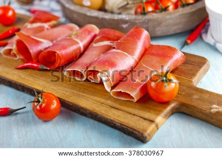 Slices of prosciutto with chili pepper and cherry tomatoes on wooden cutting board
