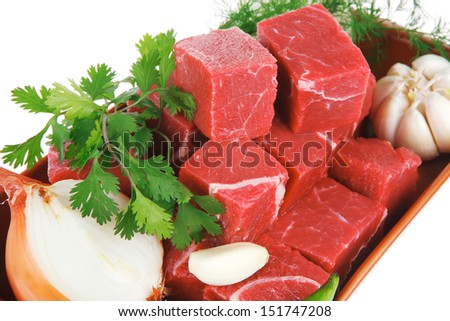 slices of raw fresh beef meat fillet in a ceramic dish with onions and peppers isolated over white background - stock photo