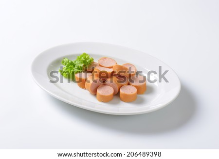 slices of raw hot dog sausage on white oval plate - stock photo