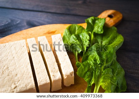 Slices of raw tofu and green leaves of fresh spinach on cutting board. Close up - stock photo