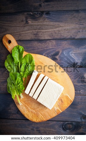 Slices of raw tofu and green leaves of fresh spinach on shabby cutting board - stock photo