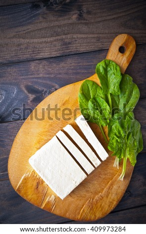 Slices of raw tofu and green leaves of fresh spinach on shabby cutting board. Top view - stock photo