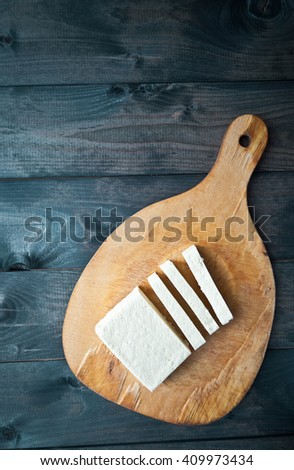 Slices of raw tofu on rustic wooden background. Top view - stock photo