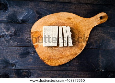 Slices of raw tofu on shabby cutting board. Top view - stock photo