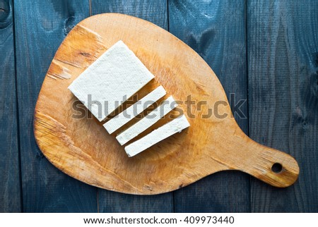 Slices of raw tofu on shabby wooden background. Top view - stock photo