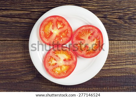 Slices of ripe tomatoes in plate on dark wooden table, top view - stock photo