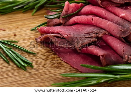 slices of roast beef with cheese and rosemary  on wooden board - stock photo