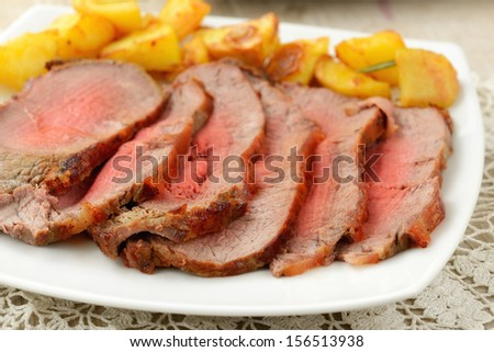 slices of roast beef with potatoes - stock photo