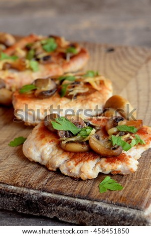 Slices of roasted Turkey meat. Fried Turkey steaks with cheese and mushrooms on a chopping board and an old wooden table. Delicious and easy meat recipe. Closeup  - stock photo