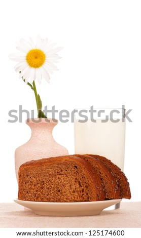 Slices of rye bread with milk on a plate on a burlap over white - stock photo