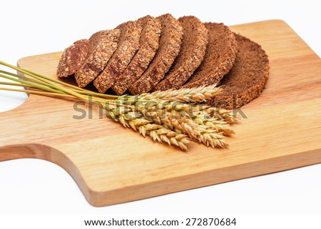Slices of rye malt bread and wheat ears on the chopping board - stock photo