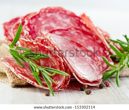 Slices of salami on wooden table. Selective focus - stock photo