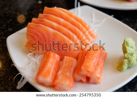 Slices of salmon sashimi and crab sticks