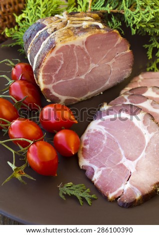 Slices of sausages and gammon ham with bread, tomatoes, herbs, garlic and basketson wooden board