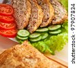 slices of savory meatloaf with vegetables cucumbers and tomatoes, lettuce, close-up - stock photo