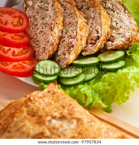 slices of savory meatloaf with vegetables cucumbers and tomatoes, lettuce, close-up
