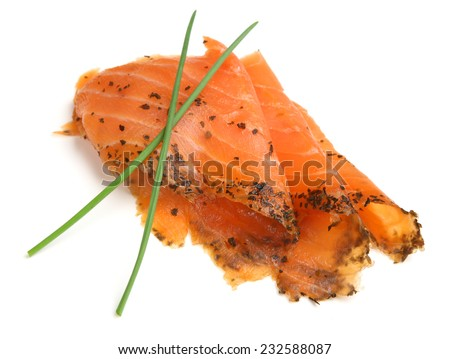 Slices of smoked salmon with basil and lemon oil.