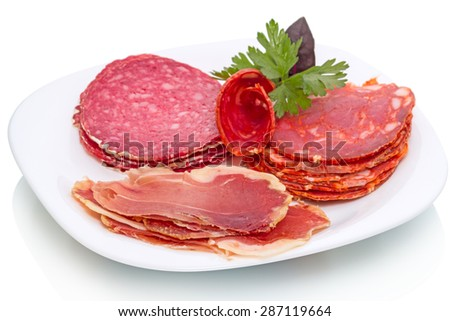 Slices of smoked sausage, meat products with parsley and basil on a white plate - stock photo
