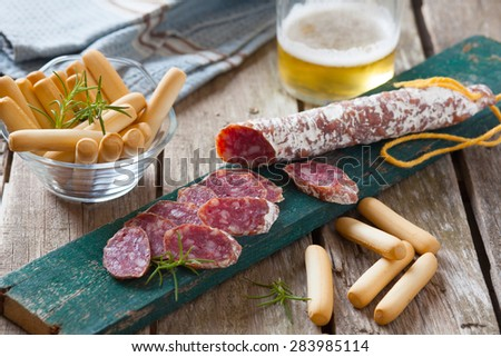 slices of spanish pork sausage on table with bread - stock photo