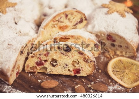 Slices of stollen on rustic wooden background with almond and orange. Shallow focus