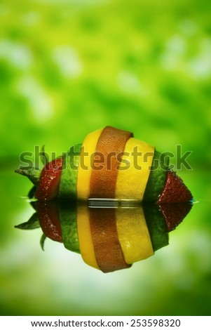 slices of strawberry cucumber, squash, and sweet potato assembled into one super fruit-vegetable mash-up on lushious green background with reflection underneath - stock photo