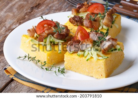 Slices of tasty polenta with meat and vegetables on a white plate on the table horizontal
