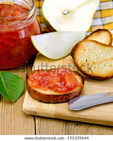 Slices of toasted bread with jam of pears, knife, green leaf on a background of wooden boards - stock photo