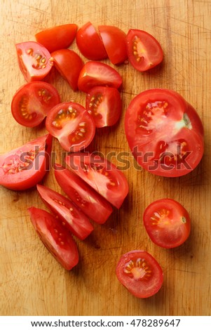 Slices of tomatoes on chopping board, food above