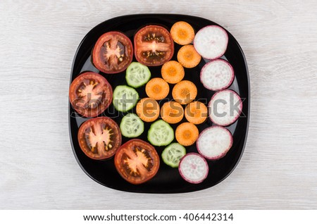 Slices of tomatoes, radishes, cucumbers and carrots in black glass plate. Top view - stock photo