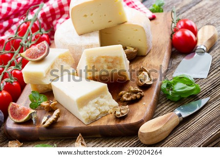 Slices of trappe and parmesan cheese on wooden cutting board with cherry tomatoes - stock photo