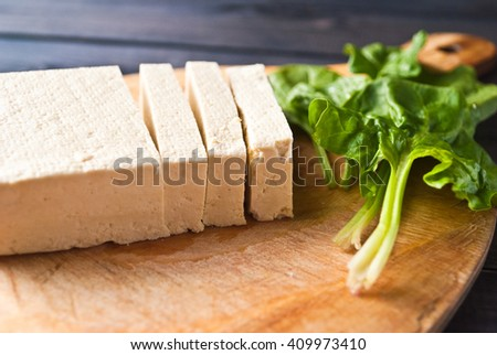 Slices of uncooked tofu and green leaves of fresh spinach on cutting board - stock photo