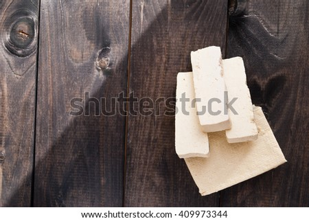 Slices of uncooked tofu on brown wooden background. Ingredient for vegetarian cuisine. Sunny day - stock photo