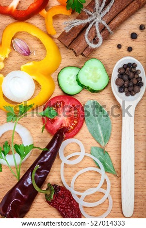 Slices of vegetables and spices on wooden table.